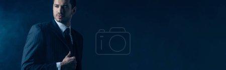 Photo pour Mafioso confiant regardant loin sur fond sombre, plan panoramique - image libre de droit