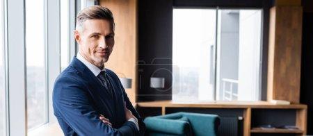 Photo pour Photo panoramique d'un homme d'affaires souriant en costume avec les bras croisés regardant la caméra à l'hôtel - image libre de droit