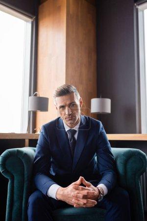 Photo pour Homme d'affaires en costume avec les mains serrées assis dans le fauteuil et regardant la caméra - image libre de droit