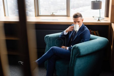 Photo for Selective focus of businessman in suit drinking coffee and sitting in armchair - Royalty Free Image