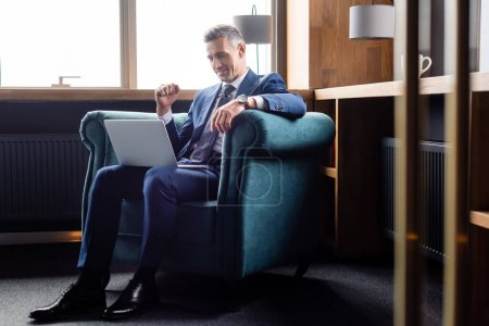 smiling businessman in suit showing yes gesture and using laptop