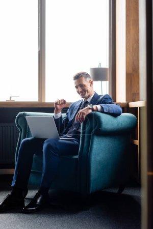 Photo pour Homme d'affaires souriant en costume montrant geste oui et en utilisant un ordinateur portable - image libre de droit