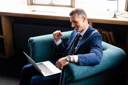 Photo pour Vue grand angle de souriant homme d'affaires en costume montrant geste oui et en utilisant un ordinateur portable - image libre de droit