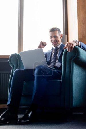 Photo pour Vue à angle bas de l'homme d'affaires en costume à l'aide d'un ordinateur portable et montrant un geste oui - image libre de droit
