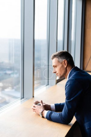 Photo pour Side view of business man in suit holding glass and looking through window - image libre de droit
