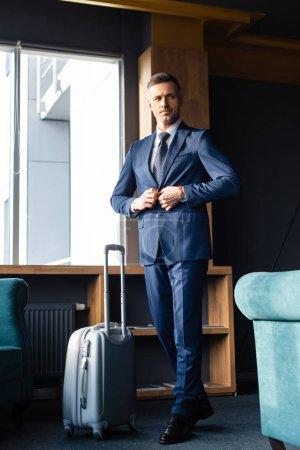 Photo pour Homme d'affaires en costume marchant près des bagages et boutonnage veste - image libre de droit