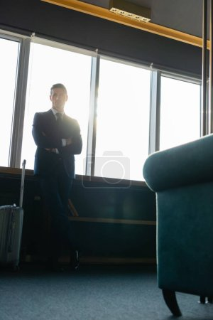 low angle view of businessman in suit with crossed arms standing near travel bag