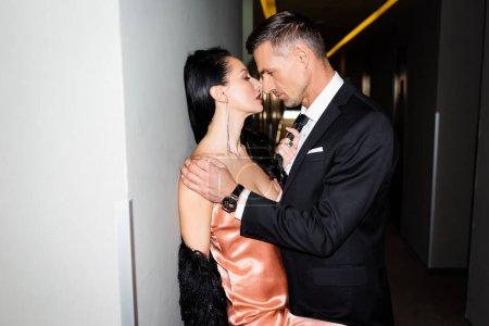 Photo pour Vue latérale du petit ami embrasser et embrasser la petite amie à l'hôtel - image libre de droit