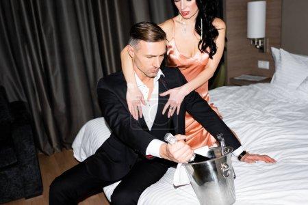 Photo pour Vue recadrée de petite amie étreignant petit ami avec bouteille de champagne à l'hôtel - image libre de droit