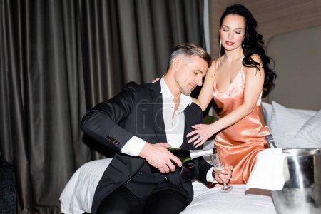 Foto de Novio verter champán y novia abrazándolo en el hotel - Imagen libre de derechos