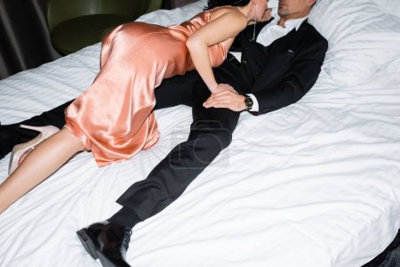 Photo for Cropped view of girlfriend in elegant dress hugging handsome boyfriend in hotel - Royalty Free Image