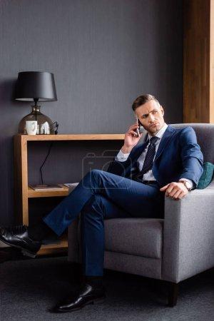 Photo pour Homme d'affaires en costume parler sur smartphone et assis dans le fauteuil - image libre de droit