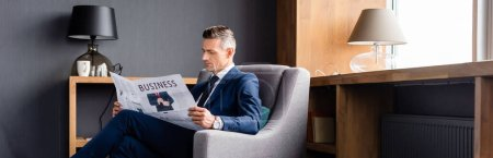 Photo for Panoramic shot of businessman in suit reading newspaper with business lettering - Royalty Free Image