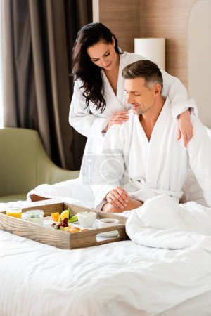 smiling girlfriend hugging boyfriend and looking at food on tray in hotel
