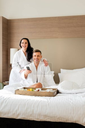smiling girlfriend in bathrobe hugging handsome boyfriend with remote controller in hotel