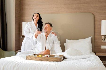 Photo pour Petite amie souriante en peignoir étreignant beau petit ami avec télécommande à l'hôtel - image libre de droit