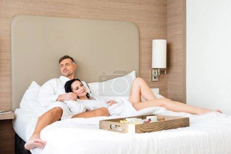 boyfriend hugging smiling girlfriend near wooden tray in hotel