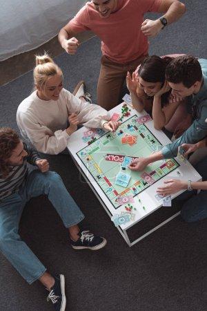 Photo pour KYIV, UKRAINE - 27 JANVIER 2020 : vue aérienne de l'homme excité montrant le geste du gagnant tout en jouant au jeu de monopole avec des amis joyeux - image libre de droit