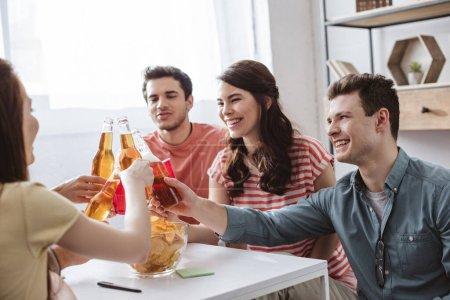 Photo pour Amis heureux cliquetis avec des bouteilles et des tasses tout en jouant jeu de nom à la maison - image libre de droit