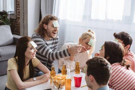 Photo pour Homme joyeux pointant du doigt tout en jouant jeu de nom avec des amis avec des notes collantes sur les fronts - image libre de droit