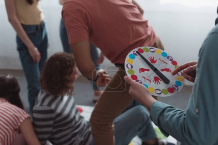 Photo for KYIV, UKRAINE - JANUARY 27, 2020: cropped view of man holding moves board near friends playing twister game - Royalty Free Image