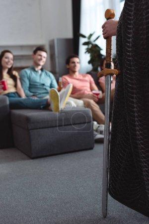 Photo pour Vue recadrée de l'homme en costume de roi de fée près des amis souriants assis sur le canapé - image libre de droit