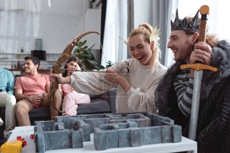 Photo pour Kyiv, Ukraine - January 27, 2020 : cheerful girl and guy in fairy costumes playing labyrinth game near bored friends sitting on sofa - image libre de droit