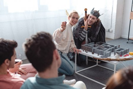 Photo pour Kyiv, Ukraine - 27 janvier 2020 : selective focus of man and woman in fairy costumes playing labyrinth game near friends - image libre de droit