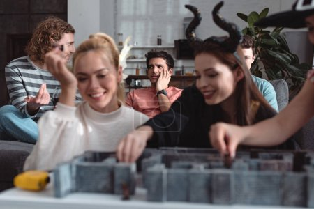 Photo pour Kyiv, Ukraine - 27 janvier 2020 : selective focus of happy girls in fairy costumes playing labyrinth board game near friends - image libre de droit