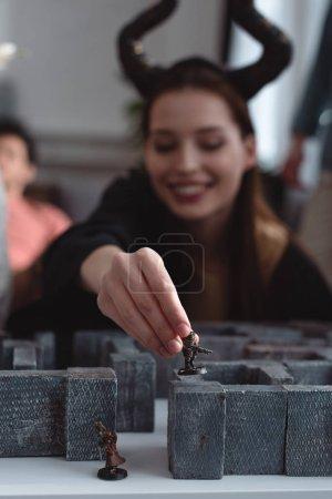 Photo pour KYIV, UKRAINE - 27 JANVIER 2020 : mise au point sélective de la fille souriante en costume avec des cornes noires tenant figurine jouet tout en jouant jeu de plateau labyrinthe - image libre de droit