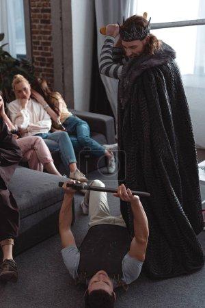 Photo pour Jeunes hommes en costumes de roi et de chevalier se battant avec des épées de jouets près des filles assises sur le canapé - image libre de droit