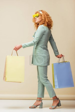 Photo for Stylish redhead woman in sunglasses with flowers holding shopping bags on beige - Royalty Free Image