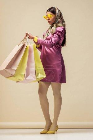 Photo pour Fille afro-américaine à la mode en lunettes de soleil avec des fleurs, foulard et robe tenant des sacs à provisions sur beige - image libre de droit