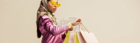panoramic shot of trendy african american girl in sunglasses with flowers and head scarf holding shopping bags isolated on beige