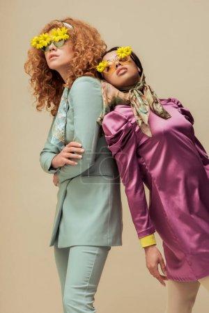 Foto de A la moda africaica americana y mujer malvada en gafas de sol con flores aisladas en beige. - Imagen libre de derechos