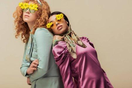 Photo pour Chic fille africaine américaine et femme frisée dans des lunettes de soleil avec des fleurs posant isolé sur beige - image libre de droit