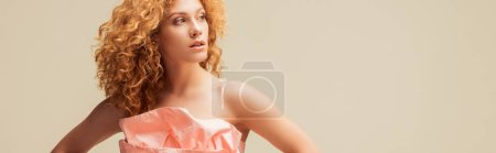 Photo for Panoramic shot of curly redhead woman looking away isolated on beige - Royalty Free Image