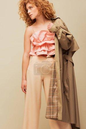Photo pour Élégante rousse femme en haut à volants et pantalon tenant trench coat tout en posant isolé sur beige - image libre de droit