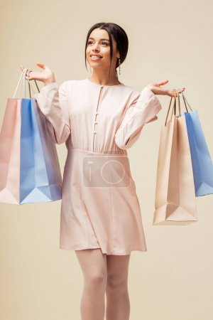 Photo for Cheerful african american girl in dress holding shopping bags isolated on beige - Royalty Free Image