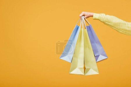 Photo pour Vue recadrée de jeune femme tenant des sacs à provisions isolés sur jaune - image libre de droit