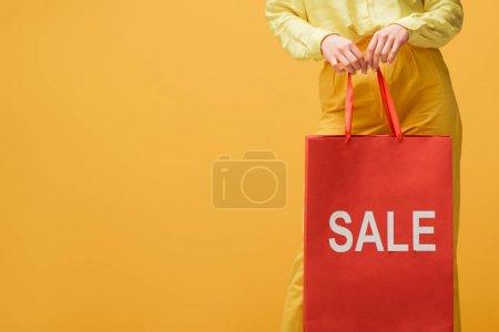 Photo pour Vue recadrée de la jeune femme tenant sac à provisions avec lettrage de vente tout en se tenant isolé sur jaune - image libre de droit