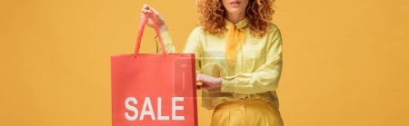 Photo pour Plan panoramique de femme rousse élégant tenant sac à provisions avec vente lettrage isolé sur jaune - image libre de droit