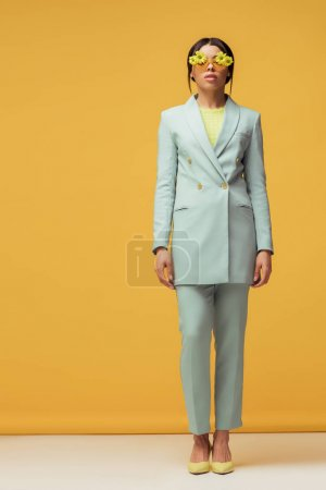 Photo for Stylish african american girl in suit and sunglasses with flowers posing on yellow - Royalty Free Image