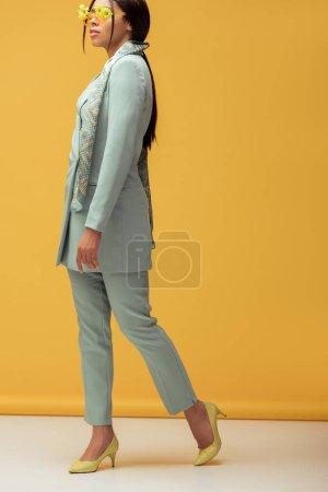 Photo pour Fille afro-américaine à la mode en costume et lunettes de soleil avec des fleurs posant sur jaune - image libre de droit
