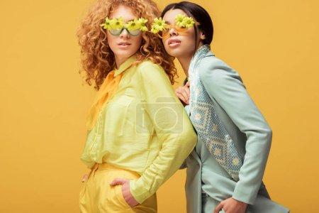 Foto de Atractivas mujeres multiculturales en gafas de sol con flores de pie con las manos en bolsillos aislados en amarillo. - Imagen libre de derechos