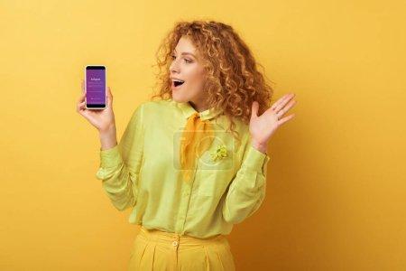 Photo pour KYIV, UKRAINE - 4 FÉVRIER 2020 : excitée rousse femme regardant smartphone avec application instagram sur jaune - image libre de droit