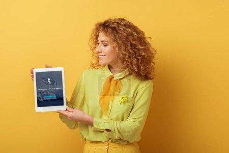 Photo pour KYIV, UKRAINE - 4 FÉVRIER 2020 : joyeuse rousse tenant une tablette numérique avec application tumblr sur jaune - image libre de droit