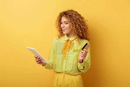 Photo for Cheerful redhead woman holding digital tablet and credit card on yellow - Royalty Free Image