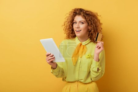 Photo for Cheerful redhead girl holding digital tablet and credit card on yellow - Royalty Free Image