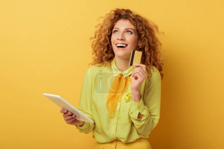 Photo for Young redhead woman holding digital tablet and credit card on yellow - Royalty Free Image